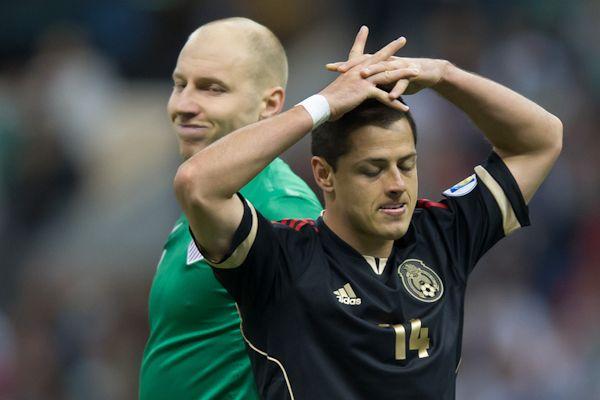 USA goalkeeper Brad Guzan and Mexico forward Chicharito Hernandez. Credit: John Todd - ISIPhotos.com