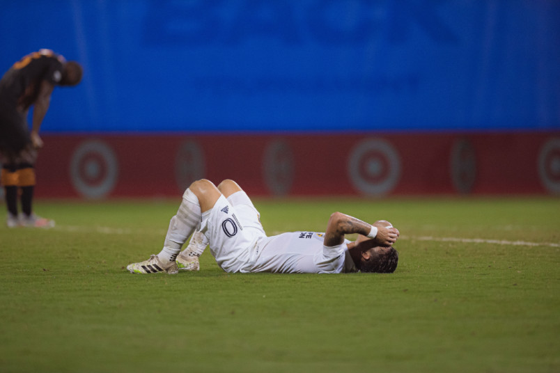 dejected galaxy and houston dynamo players laying on field