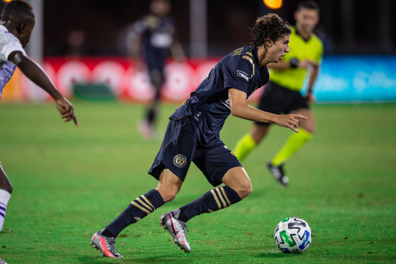 philadelphia player brenden aaronson running with the ball during mls is back