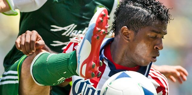 Chivas USA's Miller Bolanos tries to avoid a Portland players foot during the game on July 18th, 2012.  Chivas won 1-0.  Credit: Michael Janosz - ISIPhotos.com